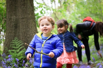 Children exploring wood in spring