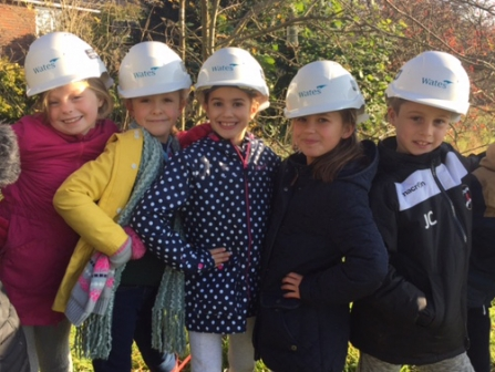School children wearing Wates hard hats