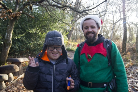 Two happy people enjoying a Christmassy walk in the woods