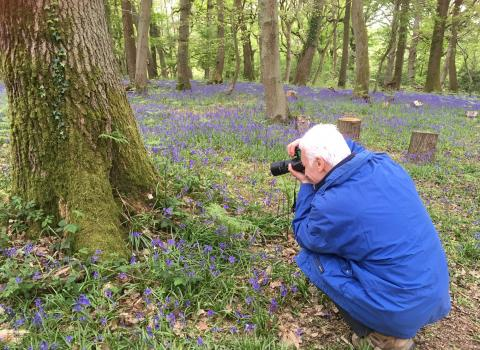 Man taking photo of bluebells on photography course